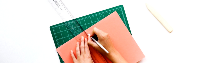 hands designing with ruler and paper